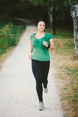 Plus size woman running in park forrest