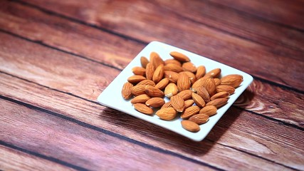 Hand put some almonds nuts on wooden table