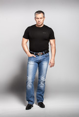 Handsome adult man in black t-shirt and jeans posing in studio
