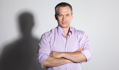 Closeup portrait of adult man in pink shirt holding arms crossed