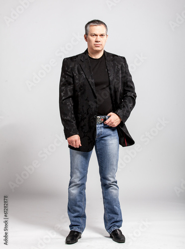 studio portrait of adult man in jeans and black jacket