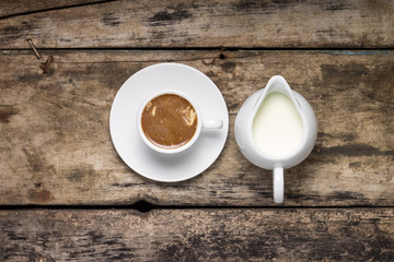 Cup of Coffee with Milk Jug on Wood Background.  Top View