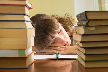 Young girl studying with books. Student sleeping during learning