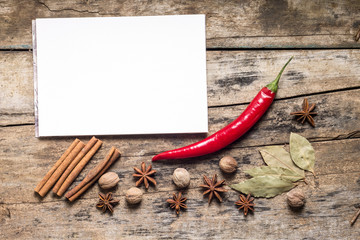 Blank White Notepad with Spices on wooden Board. Kitchen Utensil