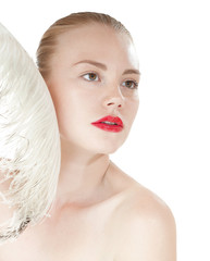 Beautiful young girl with a white feather. Spy beauty skin treat