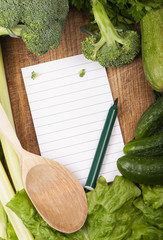 fresh vegetables on the wooden background and paper for notes