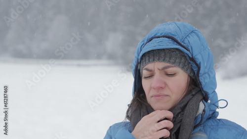 Young woman coughing in winter park