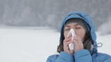 Young woman sneezes during cold day