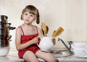 little girl in kitchen washes the dishes