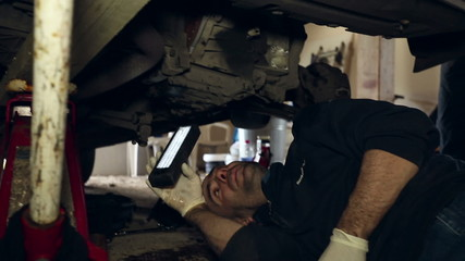Car mechanic using a light under a raised car