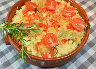 Couscous with vegetables in clay dish