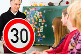 Fahrlehrer mit seiner Klasse in Fahrschule