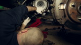 Car mechanic underneath a car fixing a clutch - Ver 2