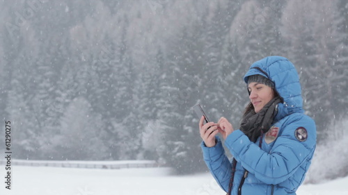 Woman texting with her phone in winter scenery, outdoors