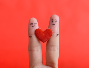 Painted finger smiley on red background, valentine concept.