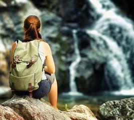 Female hiker looking at waterfall