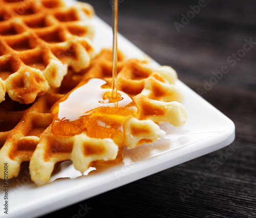 Honey pouring on a fresh waffles