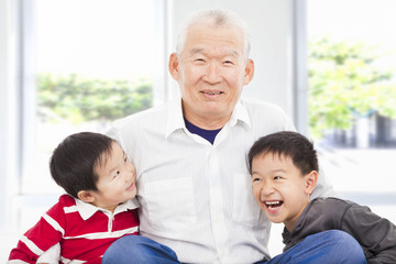 happy grandfather and grandchildren playing at home