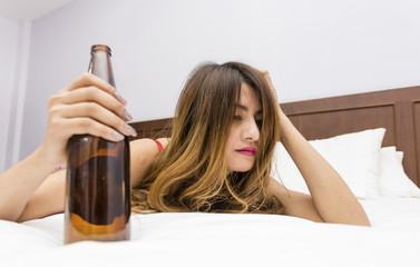 Drunk young on bed with bottle of beer in hand