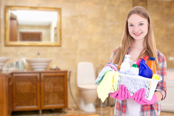 young housewife with cleaning supplies in bathroom