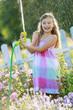 Summer fun, lovely girl has fun watering flowers