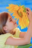 Summer - girl is smelling sunflower in the garden