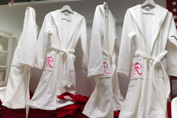 White terry bathrobes and red towels