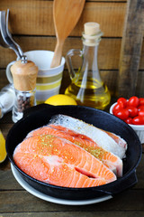 Salmon steak in a frying pan and other ingredients