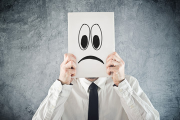 Businessman holding paper with sad face in front of his head