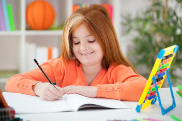 cute little red-haired girl doing her homework at home
