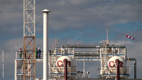 Workers on a distiller of the oil refinery.