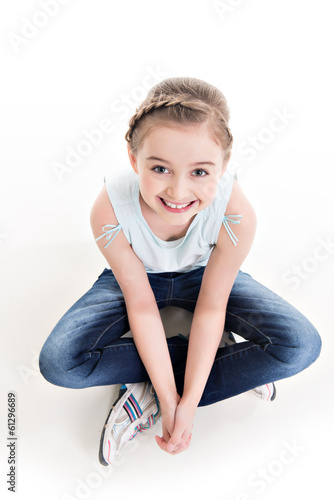 Portrait of a little girl sitting on the floor.