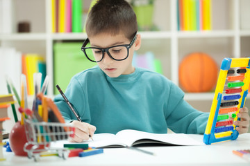 Little boy with glasess at home studying