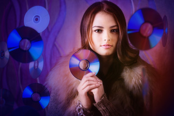 portrait of beautiful brunette girl with multiple shiny cds