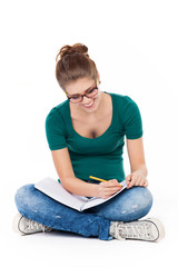 Female student sitting crossed legs, writing
