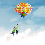 Asian couple flying with balloons