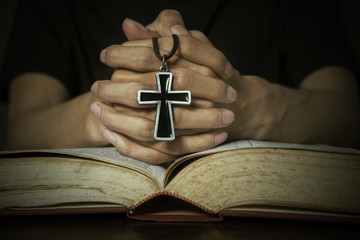 Bible and hands holding a rosary