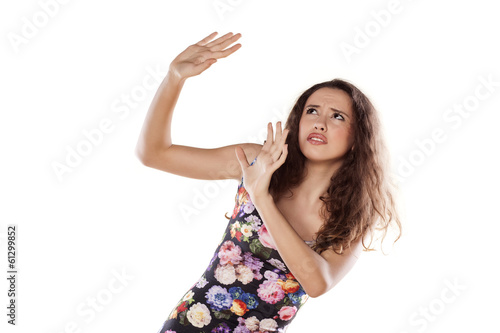 scared young girl in a defensive position on white background