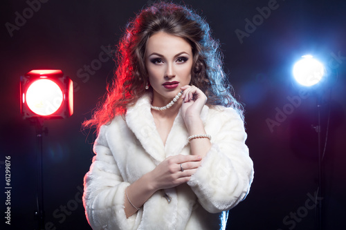 Woman in winter fur with jewellery and two lights behind