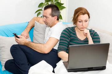 Mann mit Smartphone, Frau mit Laptop
