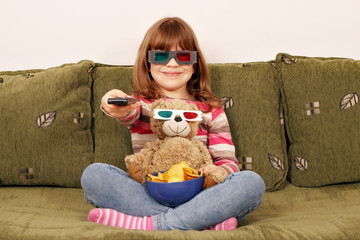 little girl and teddy bear with 3d glasses watching tv