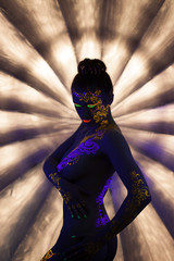 Sexy nude girl with glowing pattern under UV light