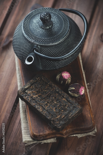 Variety of tea and asian teapot over rustic wooden background