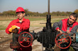 Two Skilled Oil and Gas Engineers in Action at Oil Well.