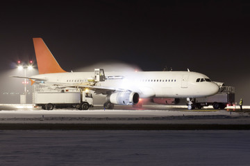 White plane with red tail during de-icing in winter