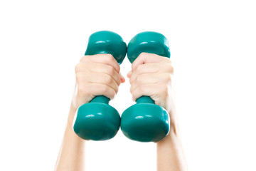 Green dumbbells in female hands