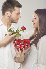 Young man giving rose and candies to his girlfriend