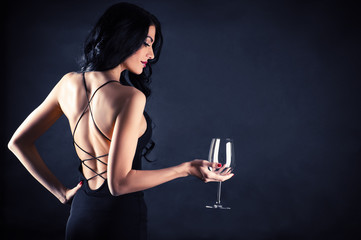 beautiful woman in a black dress with a glass in hand