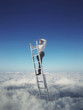 Businessman on a ladder above the clouds looking far away
