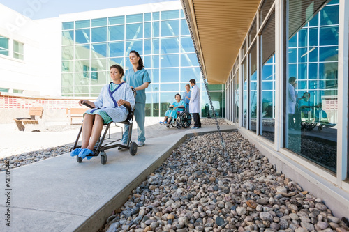 Medical Team With Patients On Wheelchairs At Hospital Courtyard - 61305441